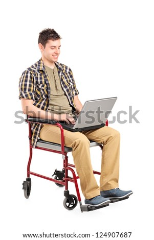 Young disabled man in a wheelchair working on a laptop isolated on white background - stock photo