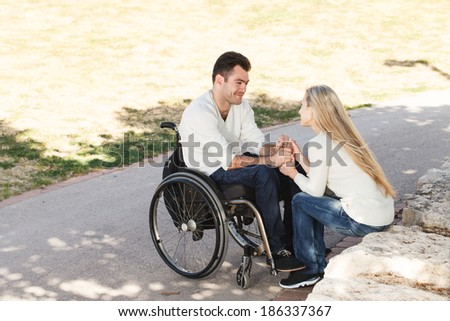 Young disabled man on a wheelchair talking with his girlfriend in the park - stock photo