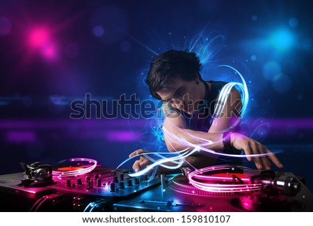 Young disc jockey playing music with electro light effects and lights - stock photo