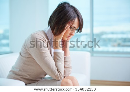 Young distraught woman sitting on sofa - stock photo