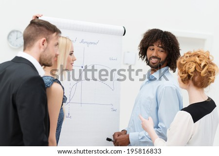 Young diverse multiethnic business team discussing analytical graphs drawn on a flip chart as they plan their forthcoming strategy - stock photo
