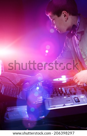 Young DJ playing records at a party in a nightclub. - stock photo