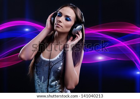 young DJ woman enjoying the music in the headphones - stock photo