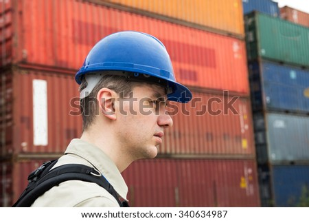 Young docker in helmet, portrait in profile. - stock photo