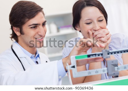 Young doctor adjusting scale for excited patient - stock photo