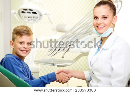Young doctor and the little boy in the dentist's office are looking into the camera. - stock photo