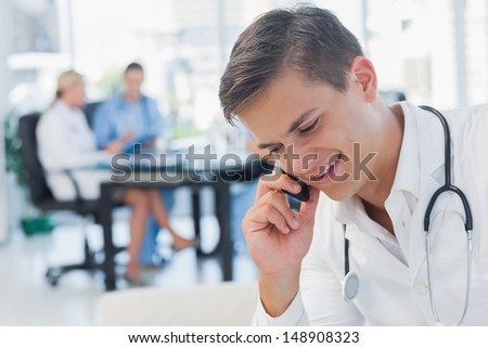Young doctor having a phone call in medical office - stock photo