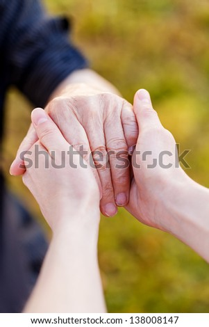 Young doctor hold elderly hands - stock photo