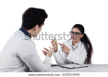 Young doctor holding pill on a little bottle and explain to her patient, isolated on white - stock photo