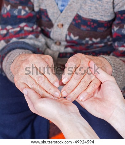 Young doctor holds the old man's hand - stock photo