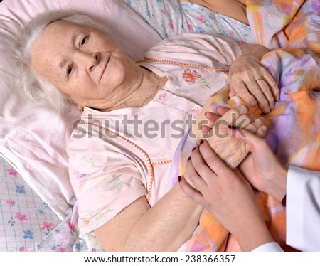 Young doctor holds the old woman's hand - stock photo
