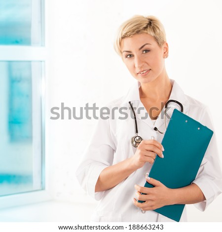Young doctor in white coat with green tablet in hospital  - stock photo