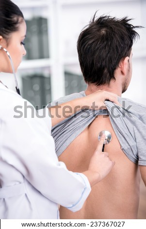 Young doctor is examining the patient lungs with a stethoscope. - stock photo