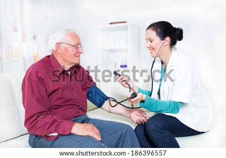Young Doctor Measuring Blood Pressure Of Senior Patient - stock photo