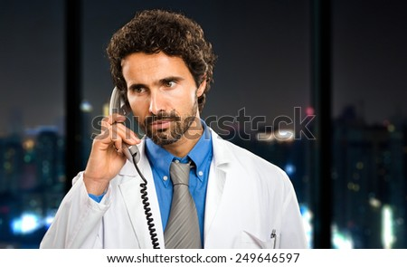 Young doctor on the phone at late night in his studio - stock photo