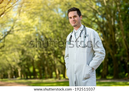Young doctor portrait with stethoscope on the green park background - stock photo