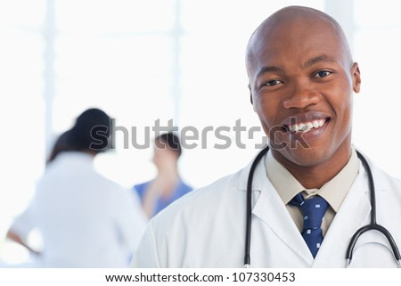 Young doctor standing with his stethoscope around his neck - stock photo
