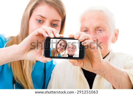 Young doctor taking a selfie with the elderly grandmother in the residential care home to send to the family. - stock photo