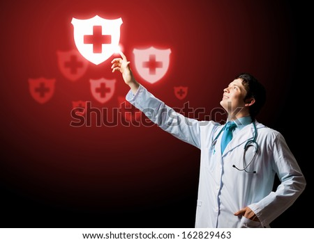 Young doctor touching with finger media medical sign - stock photo