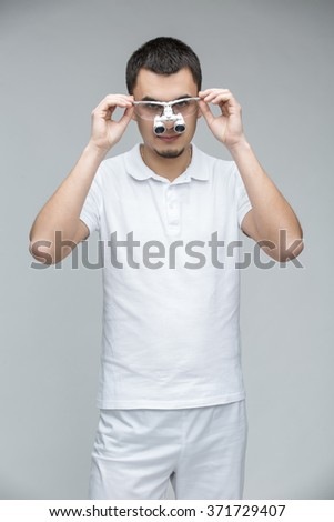 Young doctor with dental binocular loupes on his face on the gray backround. He is in a white uniform. Doctor holding his hands on loupes. Studio photo. Vertical. - stock photo