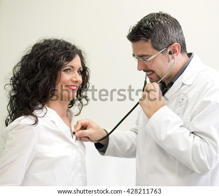 Young doctor with glasses auscultates an attractive patient - stock photo