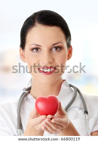 Young doctor with heart in her hand - stock photo