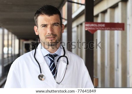 young doctor with stethoscope in hospital hall - stock photo