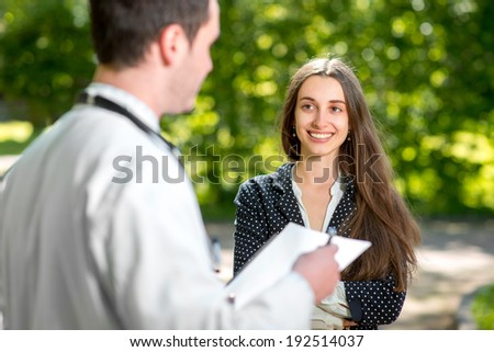 Young doctor with young and pretty woman patient or assistant speaking in the park. Treatment Outdoors. - stock photo