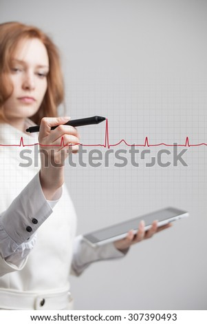 young doctor woman drawing cardiogram in air - stock photo