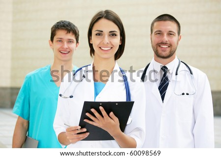 Young doctors stand against a hospital building - stock photo