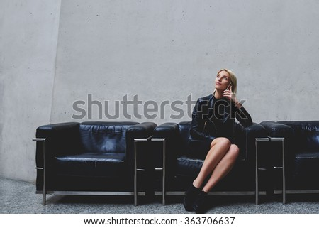 Young dreamy hipster girl having conversation via mobile phone while sitting in waiting room indoors, woman designer thinking about ideas for new project while talking with partner on cell telephone - stock photo