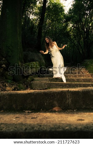 Young dreamy woman dressed in white walking in the forest - processed colors, soften effect - stock photo