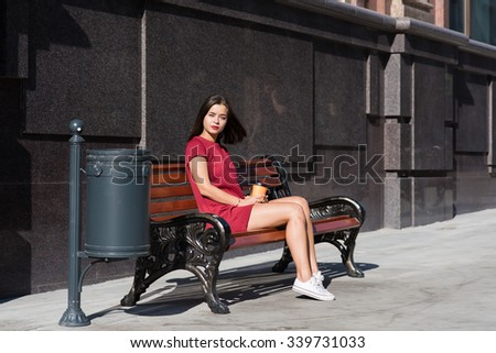 Young dreamy woman tourist relaxing after city walking while sitting on a wooden bench in the fresh air, charming brunette female thinking about something while enjoying good day and rest  - stock photo