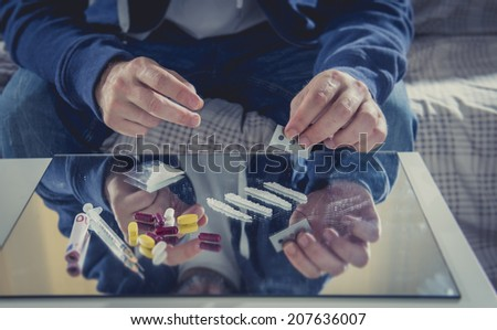 young drug addict man on hood sniffing cocaine on mirror with rolled banknote at home alone representing the concept of young people using and abusing drugs - stock photo