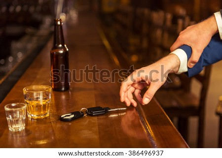 Young drunk businessman is holding a bottle of beer and reaching car keys on bar counter in pub, another man is stopping him, close-up - stock photo