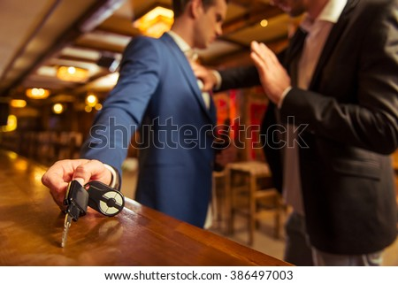 Young drunk businessman is holding a bottle of beer and reaching car keys on bar counter in pub, another man is stopping him - stock photo
