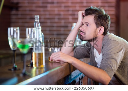 Young drunk man drinking alcohol in the bar - stock photo