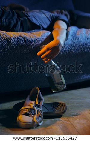 Young drunk man, lying on the couch with a bottle in hand - stock photo