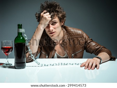 Young drunk man with a bottle of red wine / photo of youth addicted to alcohol, alcoholism concept, social problem - stock photo