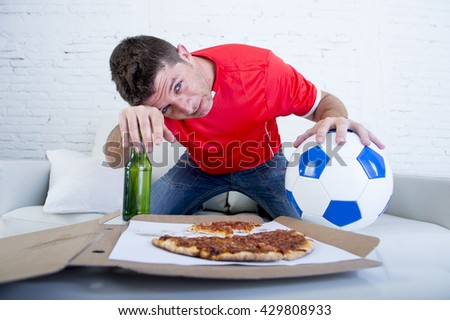 young drunk soccer supporter man holding ball and beer bottle watching football game on television sitting at home couch looking dejected , sad and disappointed for failure or defeat  - stock photo