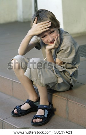 young dumpish boy, sitting on stair - stock photo