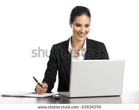 Young, dynamic businesswoman working with laptop and holding a pen - stock photo