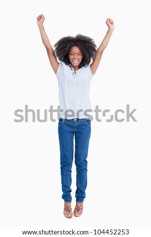 Young dynamic woman raising her arms above her head against a white background - stock photo