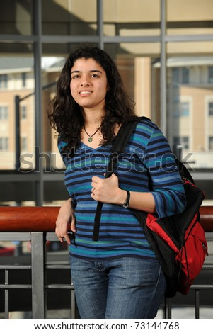 Young Eastern Student holding her backpack with College Campus buildings as background - stock photo