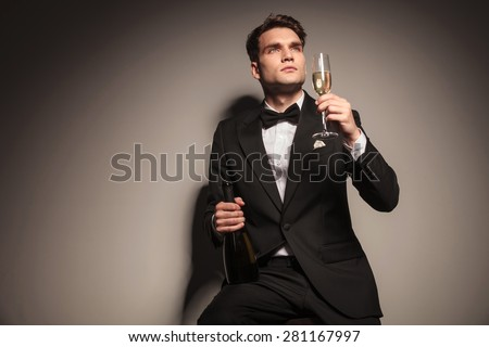 Young elegant business man enjoying a glass of champagne while siting on a chair. - stock photo