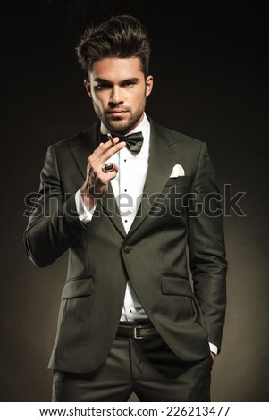 Young elegant business man looking at the camera while holding a cigarette in his righ hand and his left hand in pocket. - stock photo
