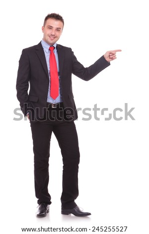 Young elegant business man standing while holding one hand in hs pocket and pointing with the other one. - stock photo