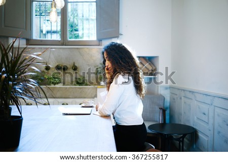 Young elegant business woman talking on the smart-phone in a cafe.attractive freelancer working with a laptop in a coffee-shop - stock photo