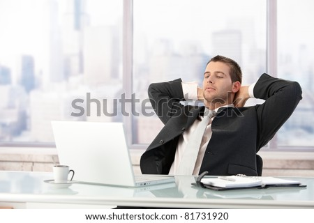 Young elegant businessman stretching on chair in office.? - stock photo