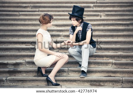 Young elegant couple on a stone stairs. - stock photo